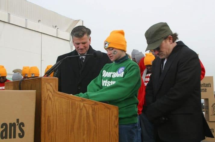 Lesley Clementi flanked by Franklin Graham (left) and musician Bono (right) pray during a special send-off for Operation Christmas Child shoebox gifts being airlifted to Uganda.