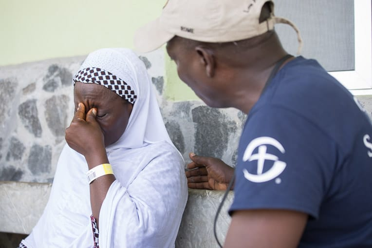 Thomas Benson comforts Fatima* as she relives the horror of the Ebola crisis.