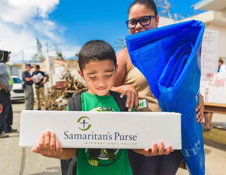 Rayda Cortes and her 6-year-old son Leon received emergency relief items during a distribution at Good Samaritan Church.
