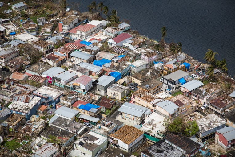 Hurricane Maria ripped off many roofs in this neighborhood near the shore of Laguna Los Corozos. Our blue shelter tarps are helping prevent further damage.