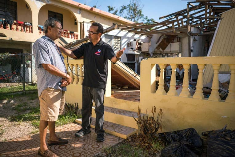 Pastor Miguel Ortiz encourages a homeowner who received a generator and tarp from Samaritan's Purse.