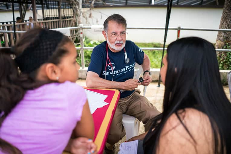 >Dr. Carlos de la Garza listened with compassion as he saw patients with a variety of ailments.