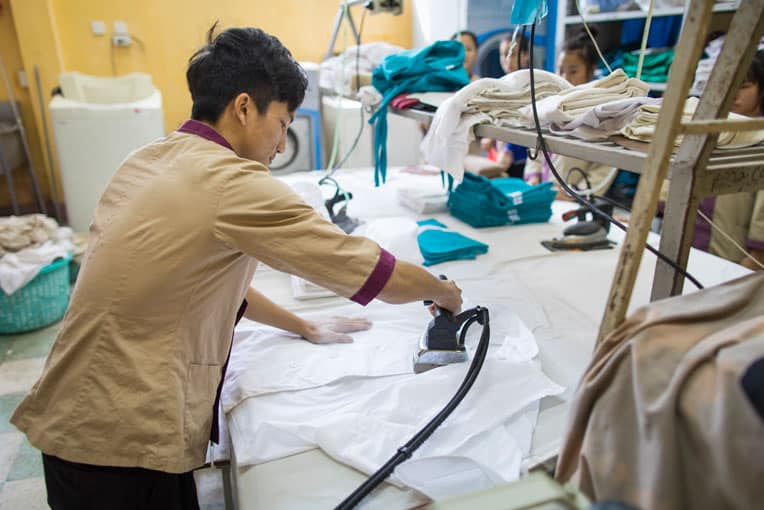 Trang is learning how to iron, fold sheets and blankets, make beds, and clean.