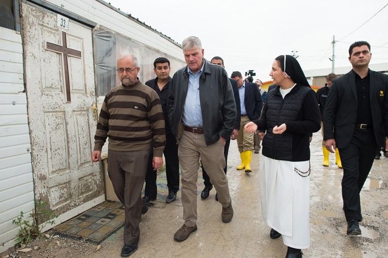 Franklin Graham walks alongside Sister Diana at a camp for Christians displaced by ISIS.