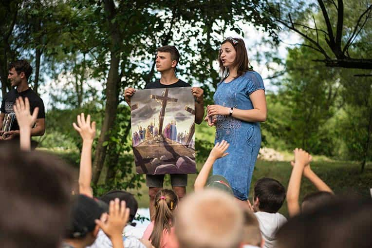 Natalya Bernik shares the Gospel with the children at Golden Generation Camp using posters from the Ministry Partner Guide before the children receive their gifts.