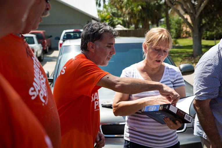 Volunteers present Marta with a Bible signed by everyone who worked on her home.