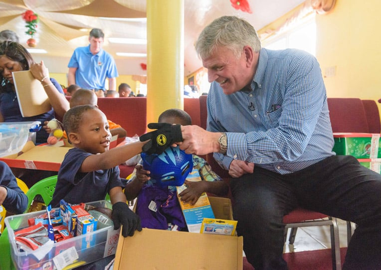 Franklin Graham helps a young boy with his shoebox gifts.