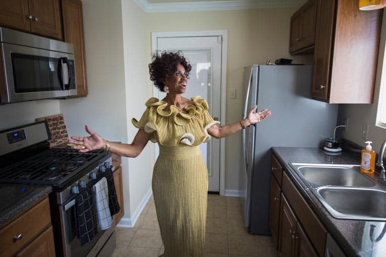 Ann Lamott is thankful for the work Samaritan's Purse volunteers did on her home. Grateful, she stands arms outstretched in her refurbished kitchen.
