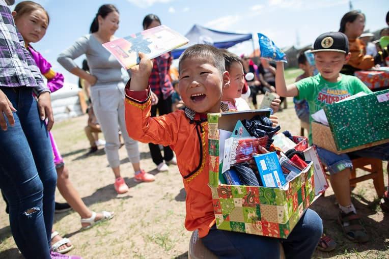 Six-year-old Khosoo delights to find a journal amid all the treasures in his shoebox gift.