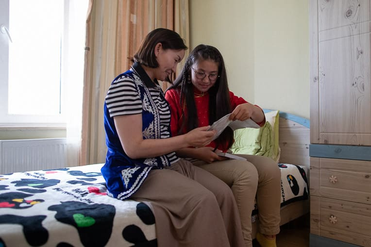 Dariya shows her mother, Saraa (left), her prayer journal and Bible from The Greatest Journey.