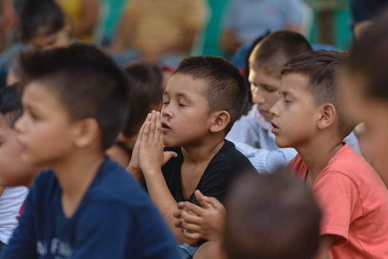 Children pray during the distribution. Will you keep these shoebox recipients in your prayers?