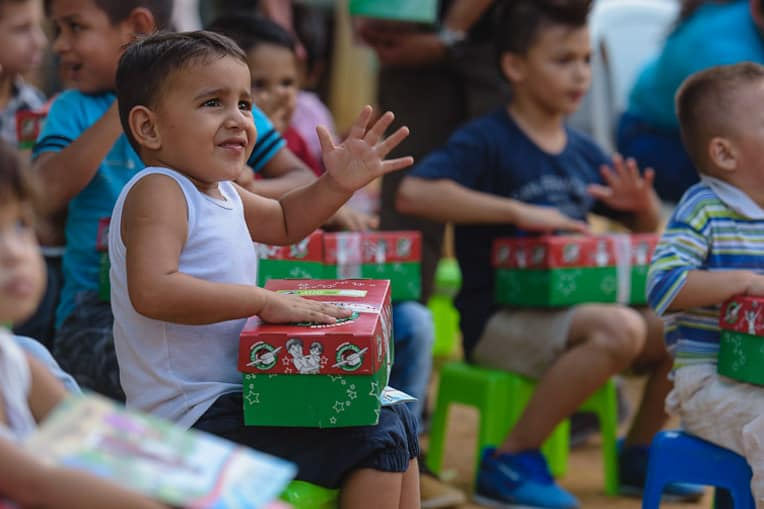 Yariana's nephew gets ready to open his shoebox gift. The family fled Venezuela as the economy collapses.