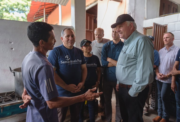 Franklin Graham meets with Jose Luis Ochoa. He was brought to Christ at the shelter and was baptized in the nearby river.
