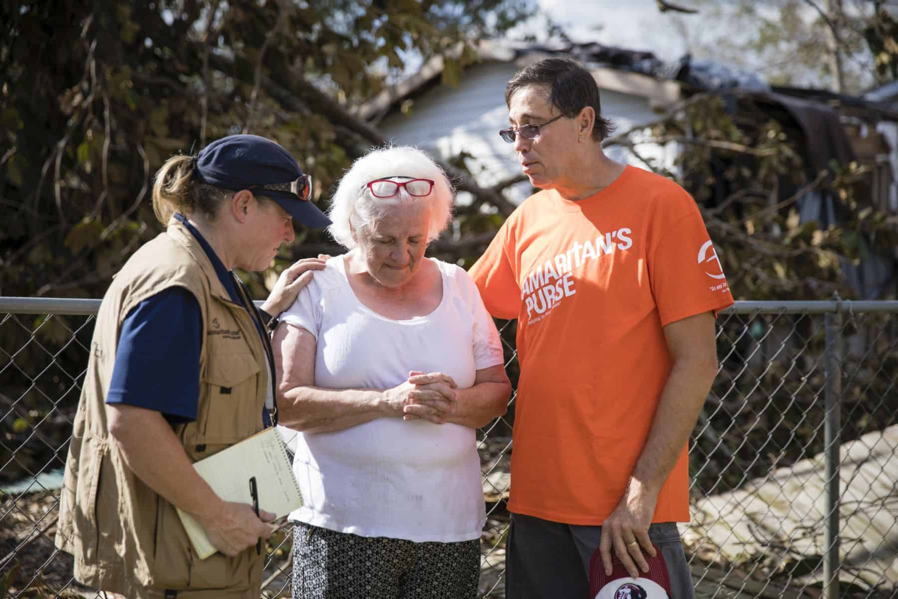 Canadian Disaster Relief Manager Tammy Suitor prays with Pastor Mike and a homeowner.