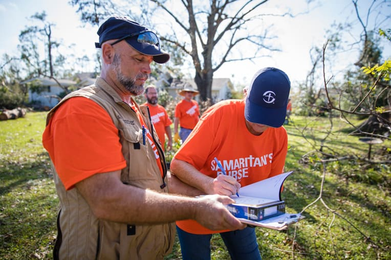 Darren Beers gathers with volunteers to sign a special Bible for homeowners in Florida.