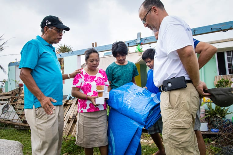 Pastor Manuelito Ray, left, of Cornerstone Community Church in Saipan prays for a family who received tarps and solar lights from Samaritan's Purse.