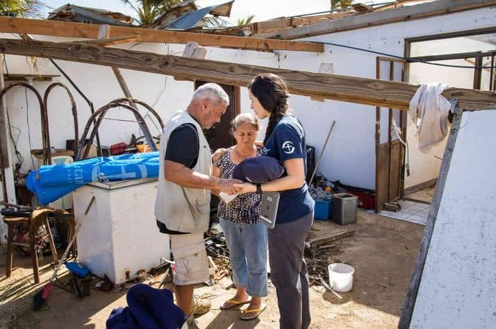Our team prays with a woman in the aftermath of Typhoon Yutu.