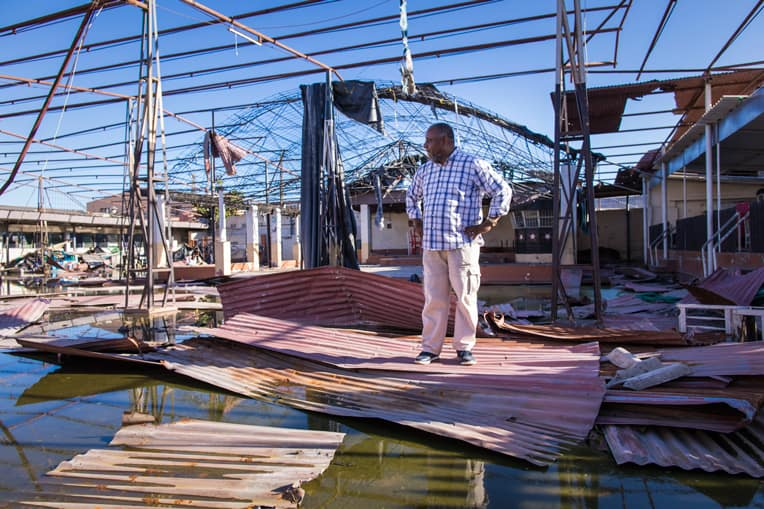 Pastor Daniel surveys the property of his church where hurricane winds and floodwaters wrecked the worship space.