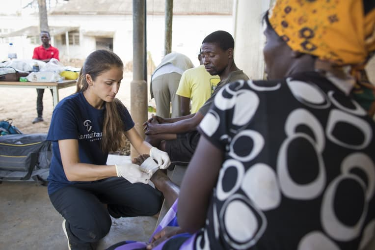 """Jessica Lutz, a Samaritan's Purse nurse, cares for Juliet Luise, a widow. Her foot was cut during the cyclone by roof metal. """"We are so grateful for Samaritan's Purse. We thank you so much for coming to visit us and give us medication."""""""