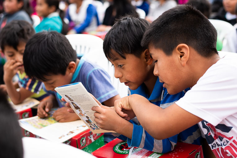 Children eagerly read The Greatest Gift Gospel booklet they received with their shoebox gifts.