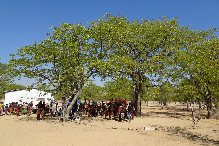 Himba villagers gather between their first church—the tree encircled by rocks—and their new church building (left).