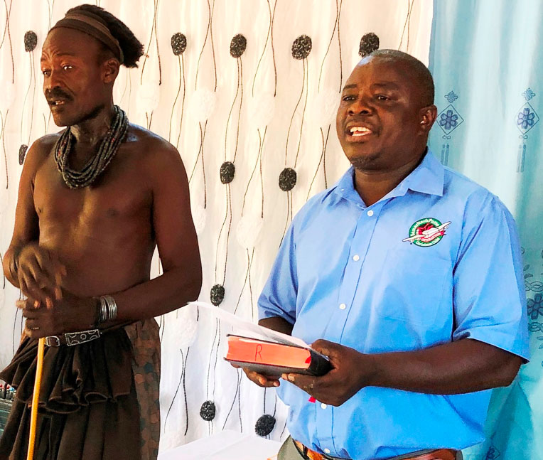 The village chief (left) who donated the land for the church spoke at the dedication ceremony while Pastor Rizera (right) translated his words for the international guests.