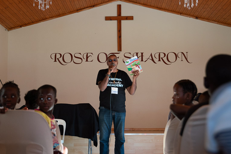 Pastor Ernest tells children of the love of God for them.