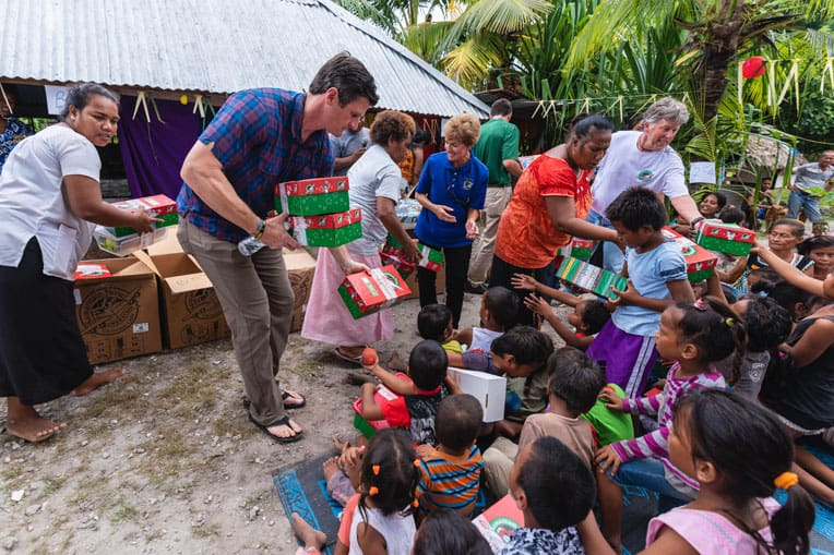 Edward Graham helps distribute shoebox gifts during an outreach event to local villages.