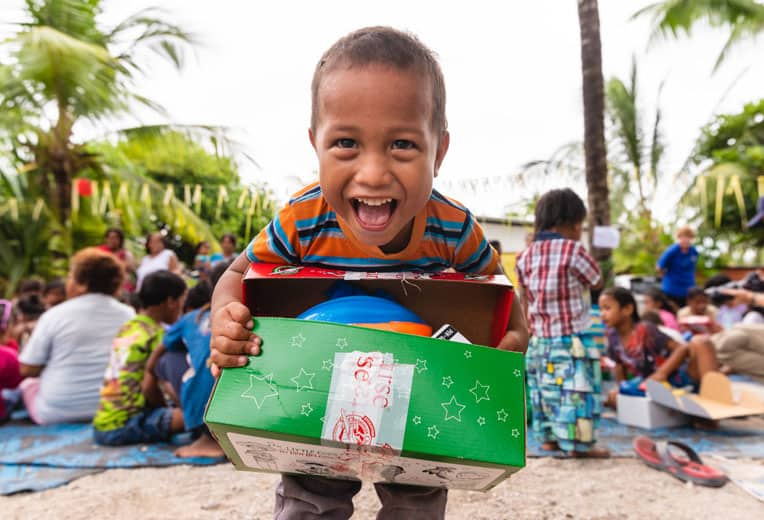 A child excitedly shows his shoebox after receiving the special gift during an outreach event in his village.
