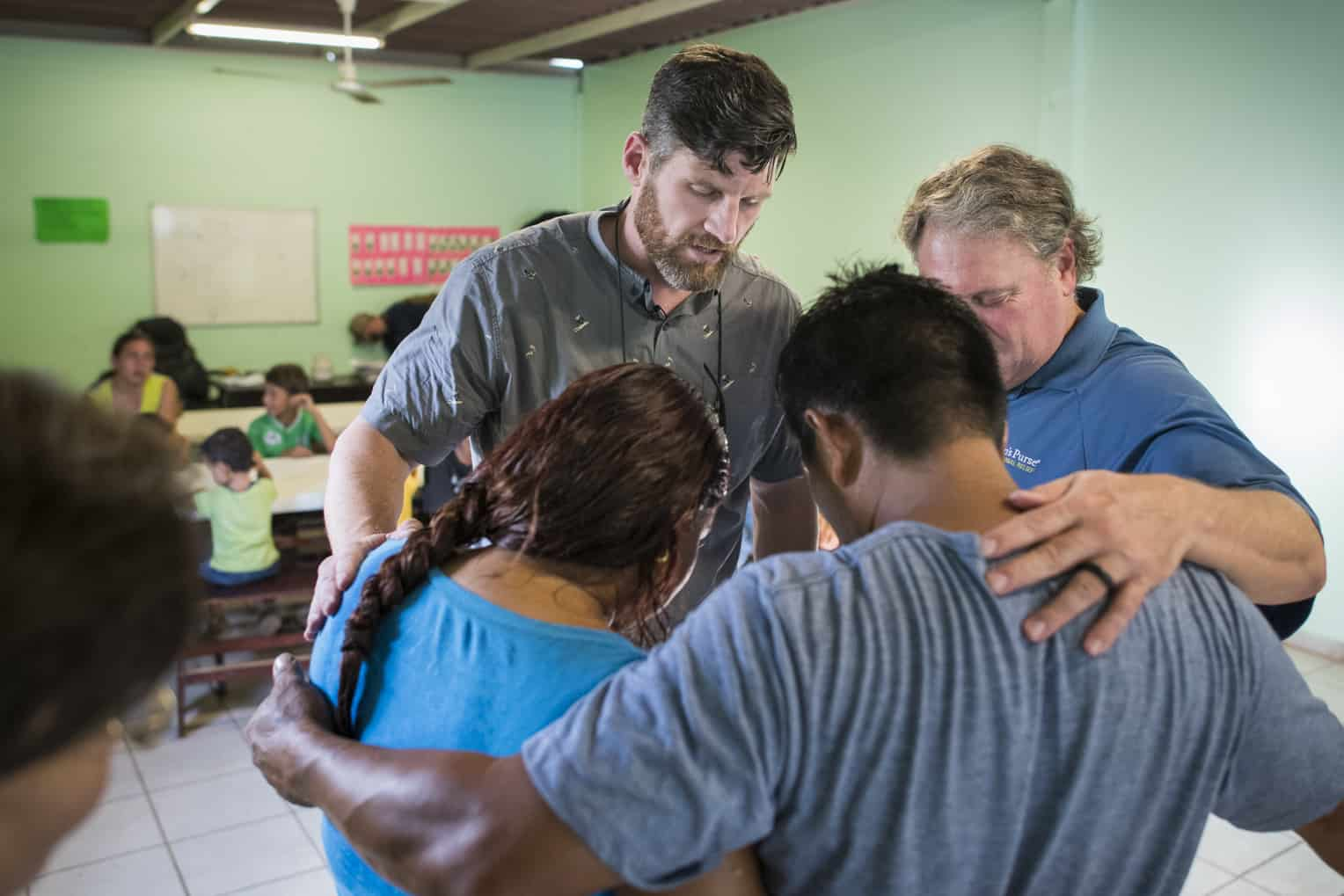 Edward Graham leads a prayer for Jesús at the feeding center.