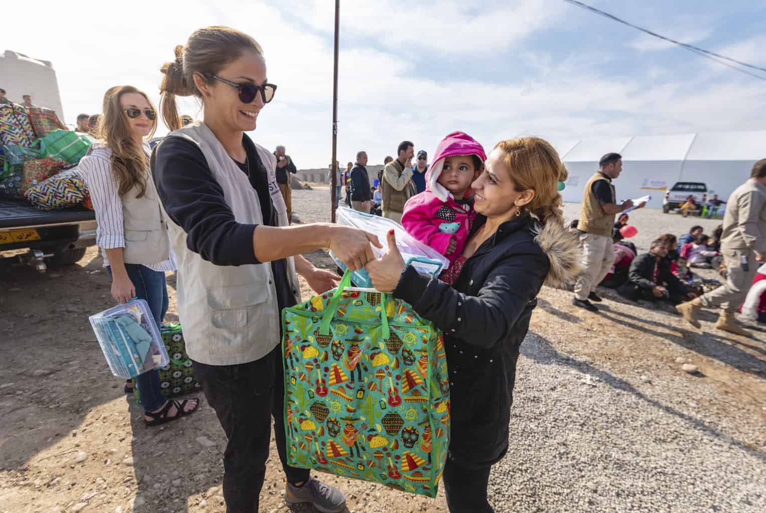 A Samaritan's Purse staff member hands out dignity and hygiene kits to Syrian refugees at Sehela transit center.