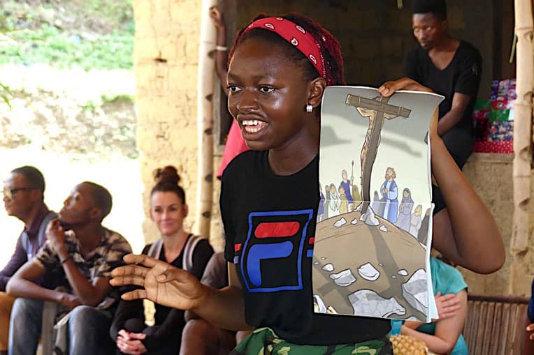 A student shares the Gospel with the boys and girls of Bolo using the Ministry Partner Guide.