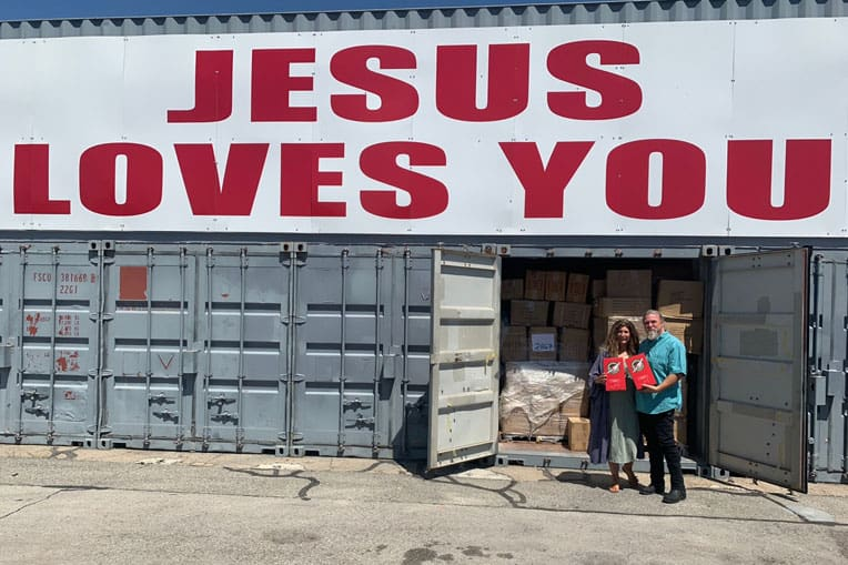 Alison Long and her husband, Terry, in front of a shipping container full of Operation Christmas Child items.