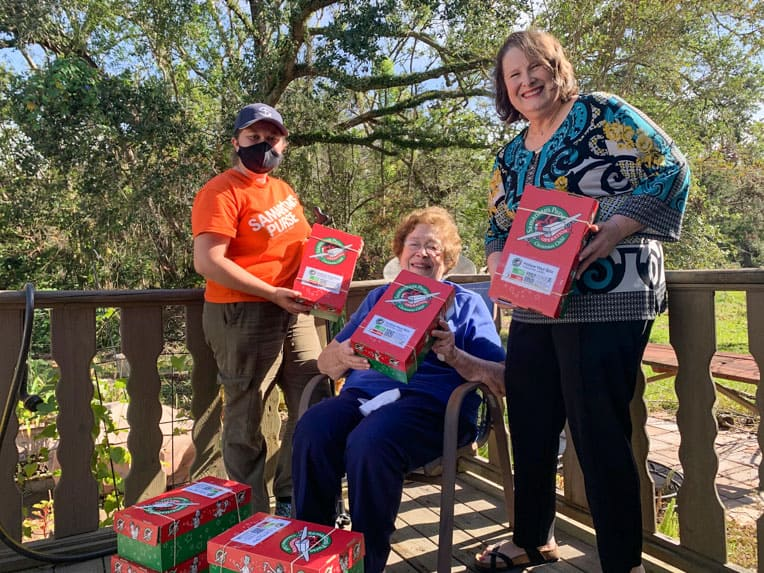 Lula (center) and her daughter Kathy celebrate the packing of Operation Christmas Child shoebox gifts with Samaritan's Purse  disaster relief volunteer Joslyn Baergen.