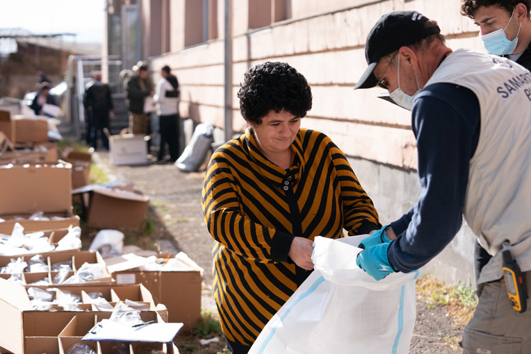 Nazely collects winter clothing items for her family at the Samaritan's Purse distribution in Vardenis, Armenia.