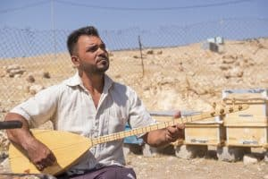 A Yazidi serenades the bees he received from Samaritan's Purse.