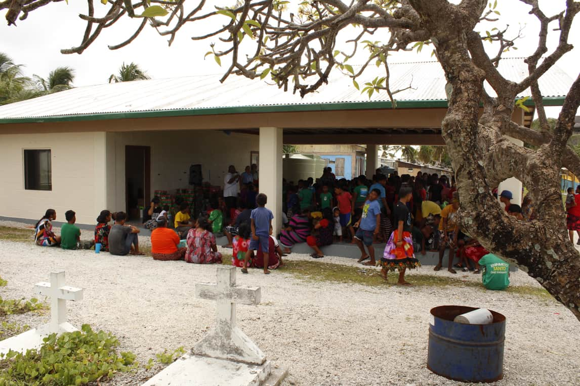 Children gathered under a covered patio while their parents gathered around the edges.
