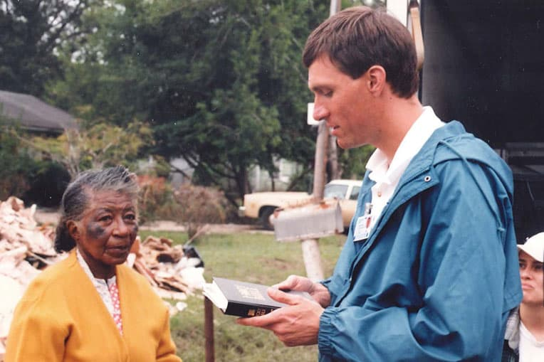 Luther Harrison, current vice president of North American Ministries, presents a Bible to a flood victim in Victoria, Texas in 1998.