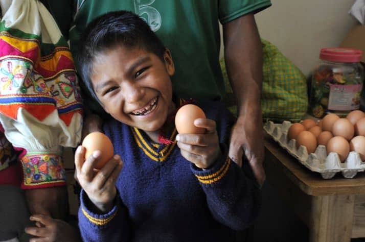Andy, 7, proudly shows off the eggs his parents sell at their store.