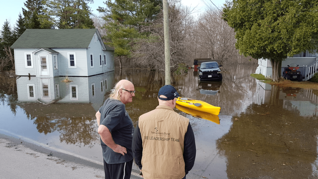 Andy Northup, a site leadership team member, speaks with a local homeowner as our team assesses the flood damage.
