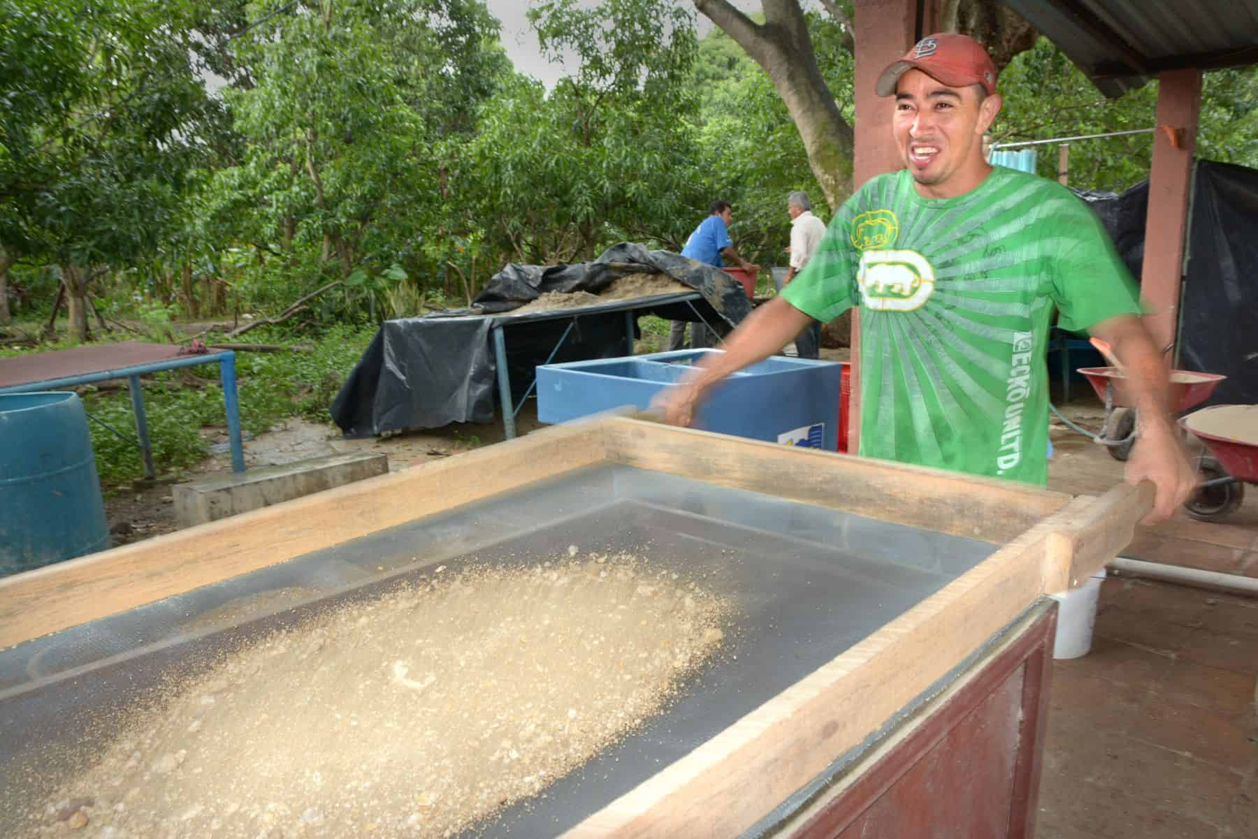 BioSand Filter recipient Dimas sifts the sand that is a key component of BioSand Filters.