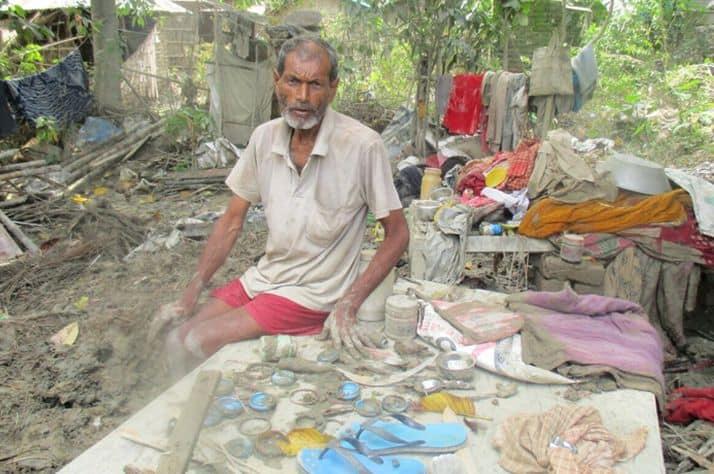 A Nepali man sorts through his few belongings that remain after devastating floods.