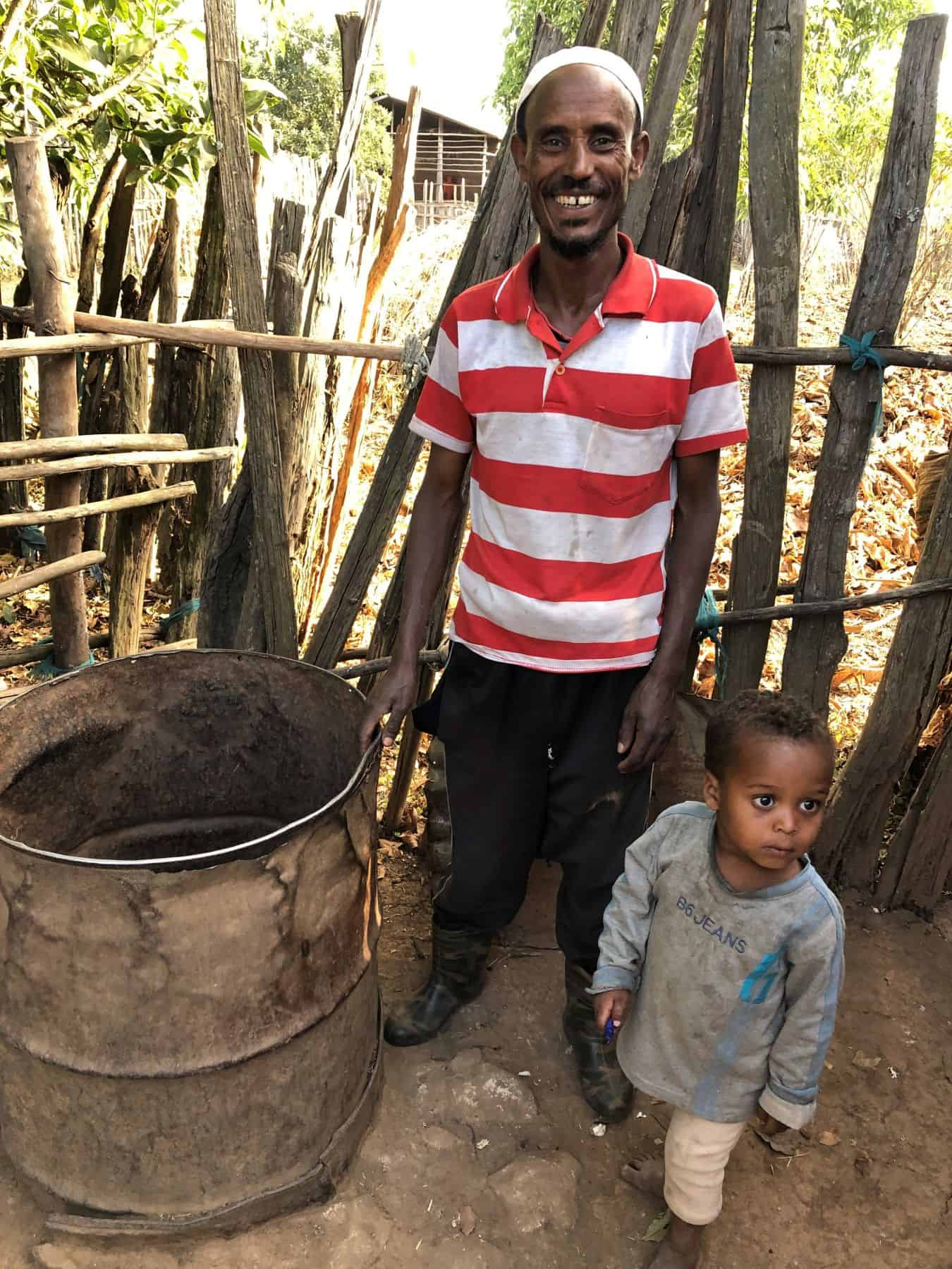 Dinake Hussan smiles while standing with his son beside their family well, knowing their BioSand Filter is making the well water safe to drink