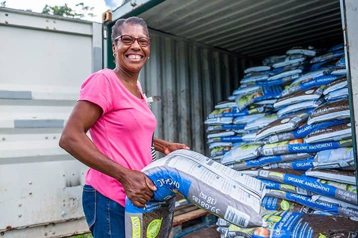 Gilles unloads fertilizer from Samaritan's Purse to aid her crops.