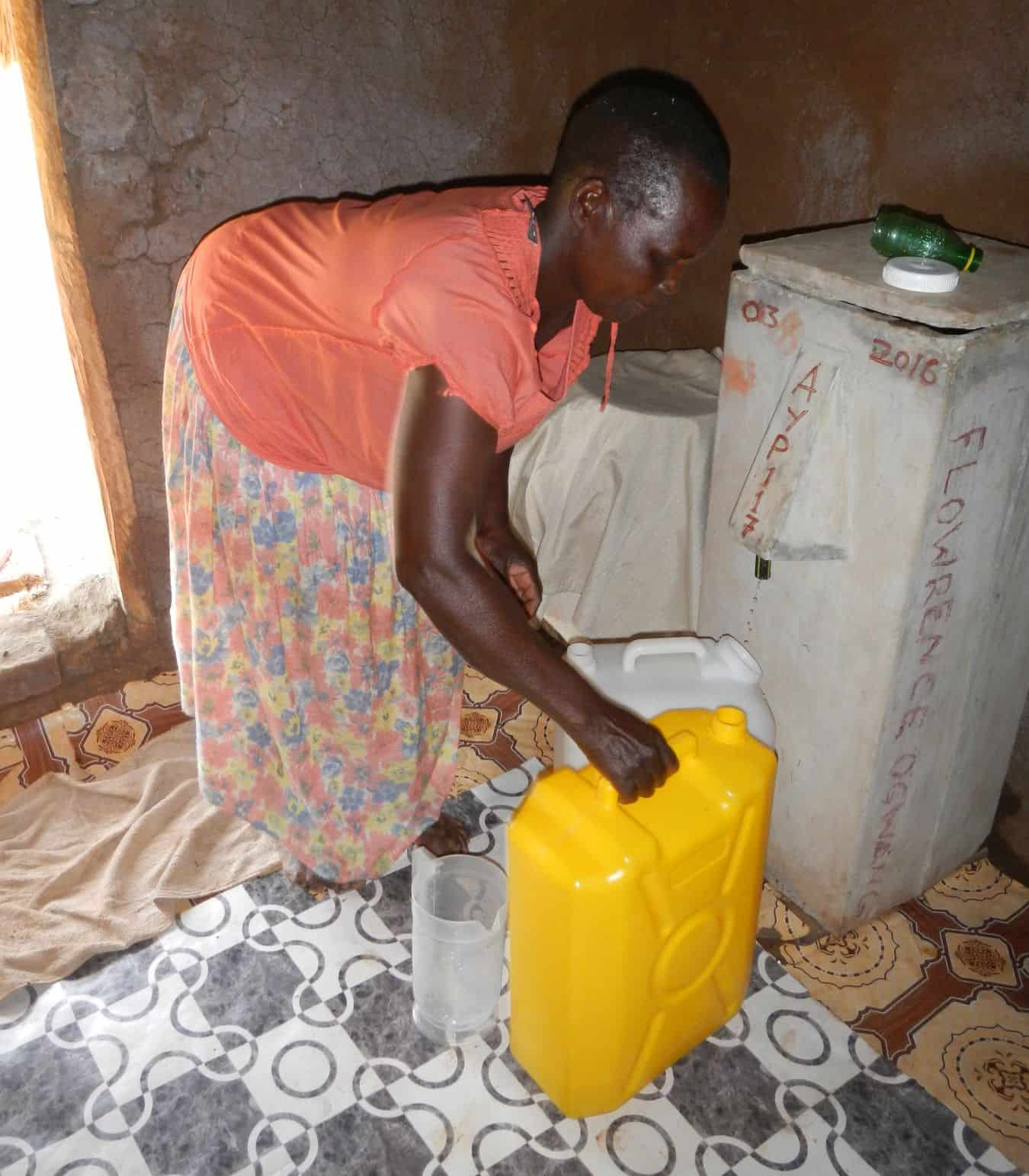Florence Akullo gathering filtered water from her BioSand Water Filter.