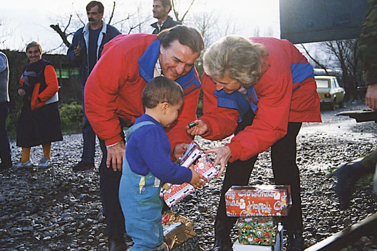 Pastor Ross and Carol Rhoads hand out shoebox gifts to children in Bosnia in 1993.