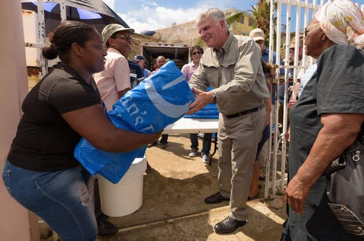 Samaritan's Purse International President helps distribute heavy-duty shelter plastic in Puerto Rico on Monday.
