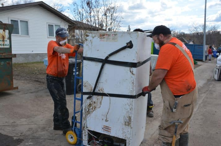 Samaritan's Purse volunteers move a fridge filled with rotting food out of a Fort McMurray house to the curb for pickup.