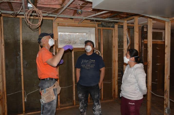 A Samaritan's Purse staff member shows Fort McMurray homeowners Garry and Charity Jimenez the work done to prepare their flood-damaged basement for repair.