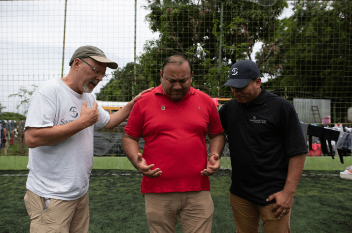 Samaritan's Purse staff John Freyler (left) and Angel Jordan (right) pray with Pastor Marlon Hamilton, one of our local partners.